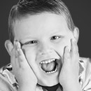Young boy laughing with hands on cheeks