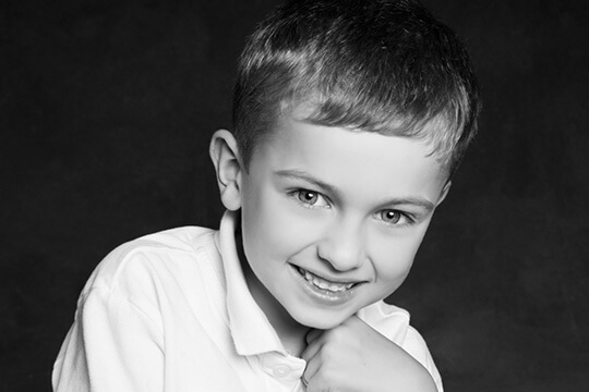 Young boy with healthy teeth posing chin on hand