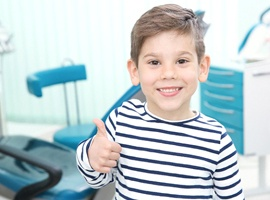A little boy wearing a striped shirt and giving a thumbs up after completing a fluoride rinse