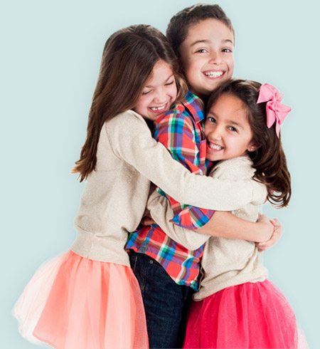 Three smiling kids hugging