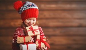 A little girl holding Christmas presents
