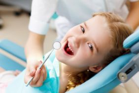 A little girl with red hair seeing a pediatric dentist